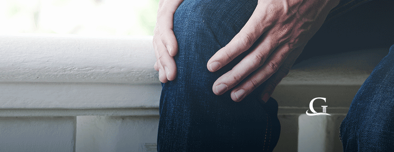 Man Holding Knee In Pain Stock Photo
