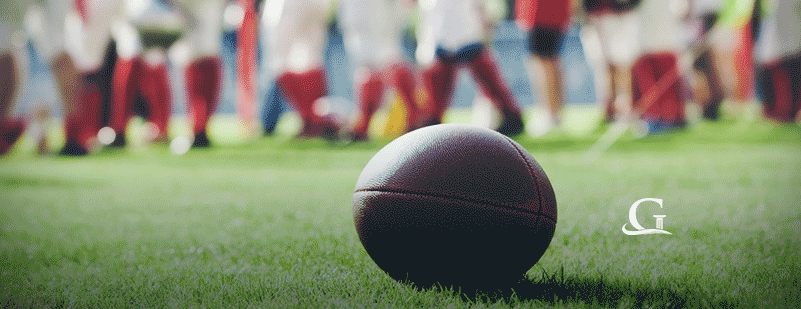 Football Laying On The Grass During A Football Game Stock Photo