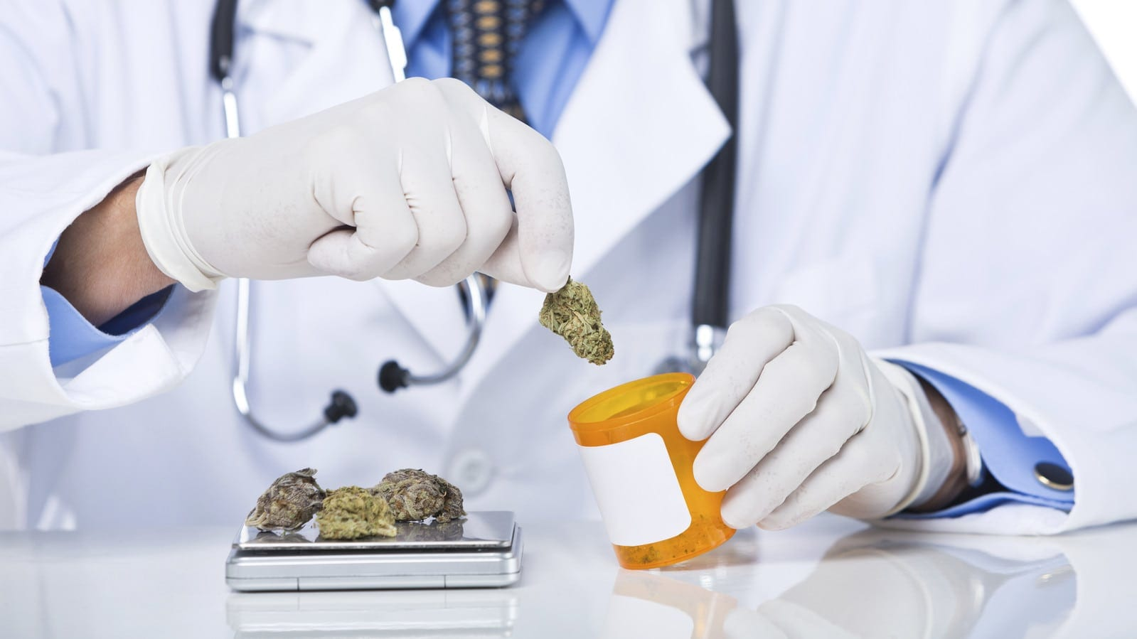 Part of a senior doctor holding pill bottle with scale and marijuana, isolated on white background