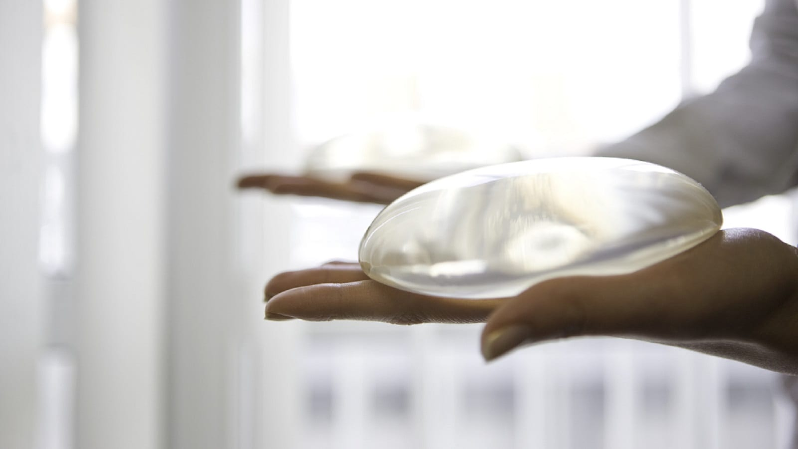 Surgeon Holding Two Breast Implants