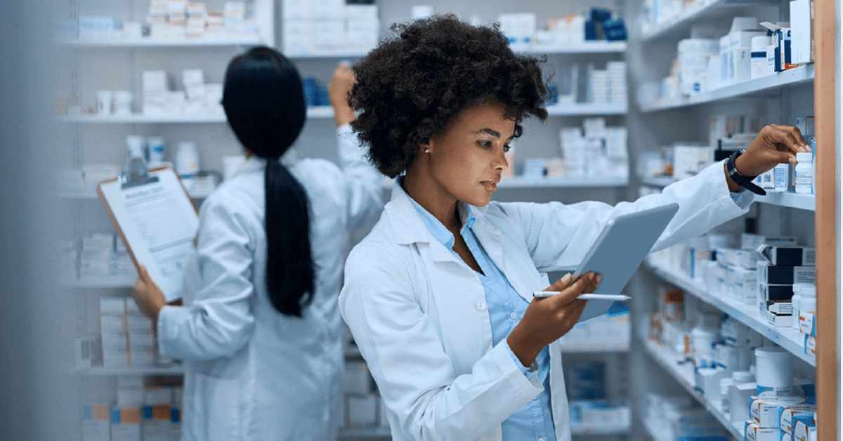 Female Pharmacist Examining Medication Bottles Stock Photo