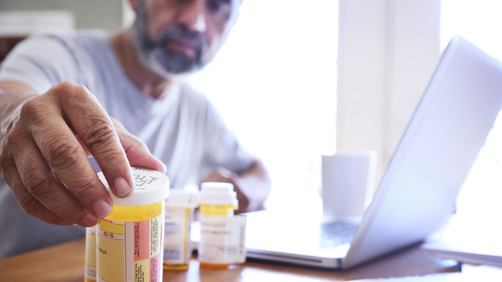 Mature Man Reaching For Prescription Pill Bottle