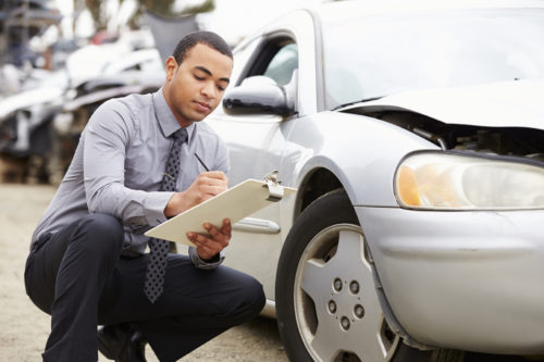 insurance adjuster inspecting vehicle damage after an accident in Phoenix, AZ