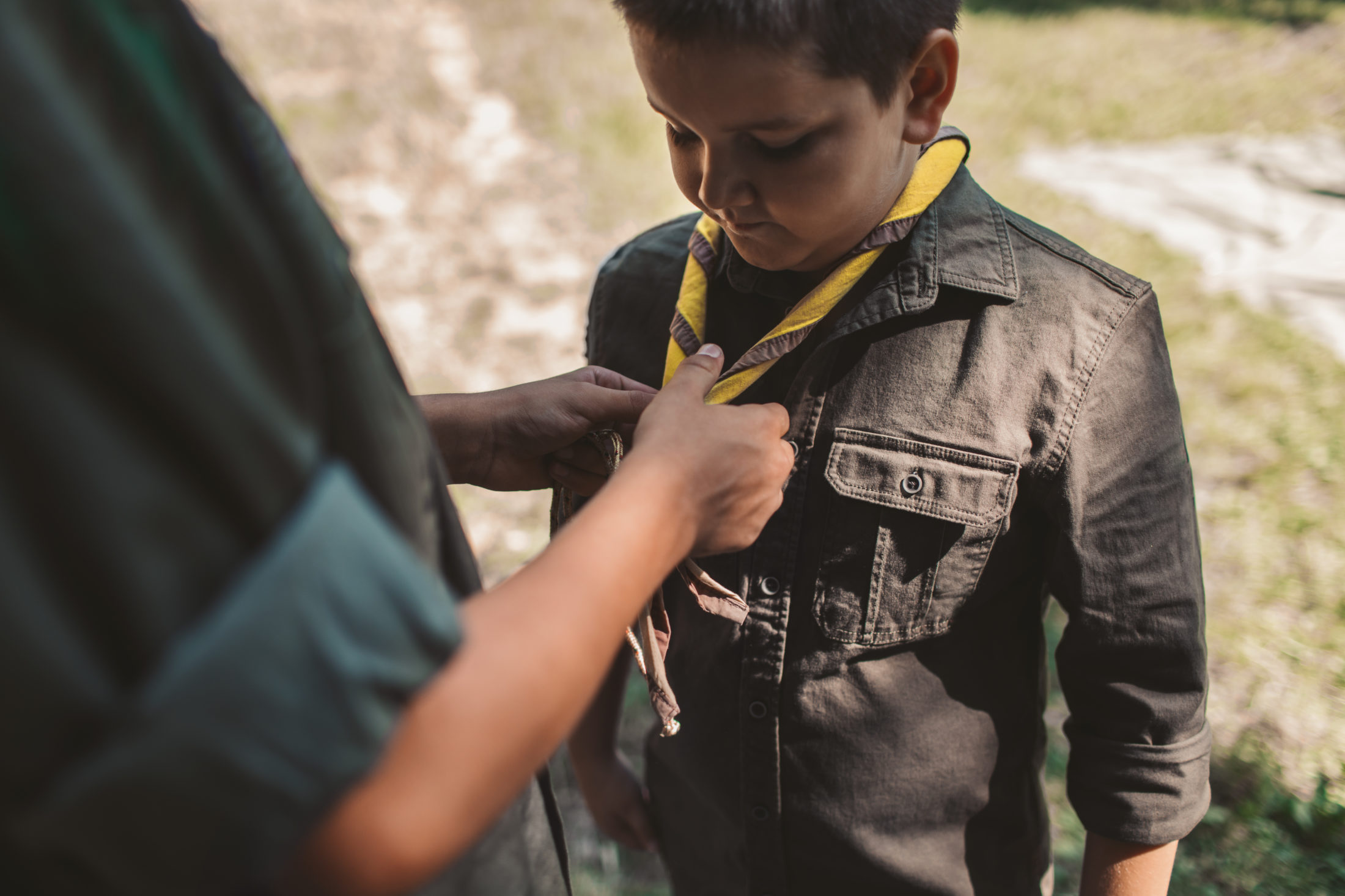 boy scout having his scarf tied by scout leader